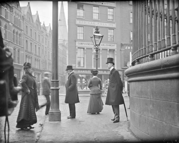 Man with umbrella standing at the junction of Nassau Street, Grafton Street and Suffolk Street. View from Nassau Street at the corner of ...