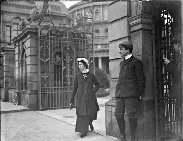 Woman wearing orthopaedic shoe, walking through the gates of Leinster House, Kildare Street. Man standing to the left of the woman, National...