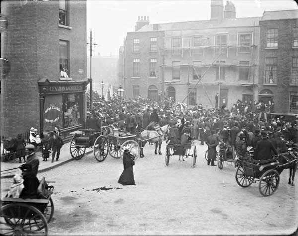Funeral procession passing through Berkeley Street. View from Blessington Street of a crowd of mourners gathered around a horse-drawn funeral...