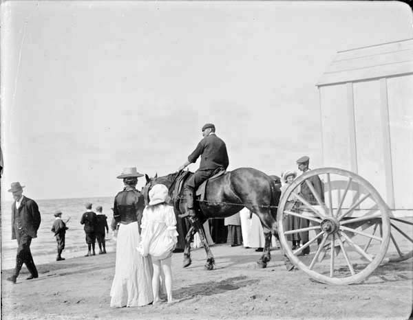 Horse-drawn bathing box. Horse-drawn bathing box being brought towards the sea, possibly at Bray. Men, women and children observing