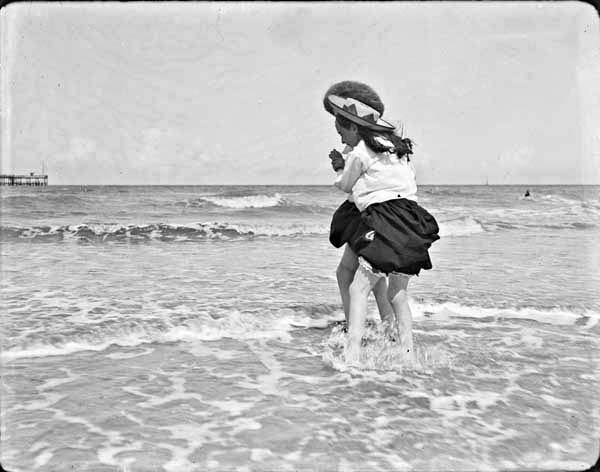 Two girls playing in shallow water at the seaside with backs to the camera