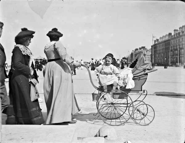 Two women and one man walking with perambulator and infant. Women pushing perambulator has face turned away from the camera, infant sitting...